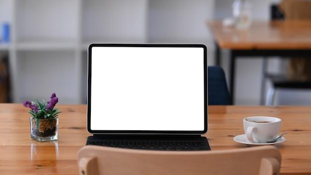 Widok z przodu komputera typu tablet z pustym ekranem, filiżanką kawy i rośliną na drewnianym biurku