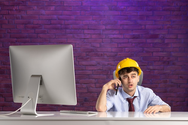 Widok z przodu konstruktor płci męskiej za biurkiem rozmawia przez telefon