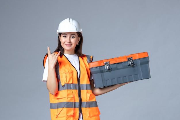 Widok z przodu konstruktora trzymającego walizkę narzędziową na szarej ścianie