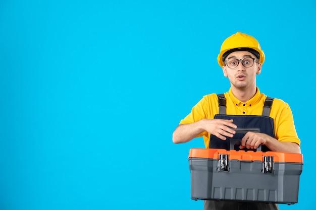 Widok z przodu konstruktora w mundurze z skrzynką narzędziową w rękach na niebieskiej ścianie