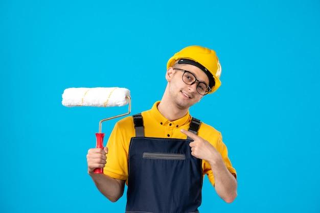 Widok z przodu konstruktora w mundurze z wałkiem do malowania w dłoniach na niebieskiej powierzchni