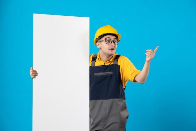 Widok z przodu konstruktora w żółtym mundurze i hełmie z planem na niebieskiej ścianie