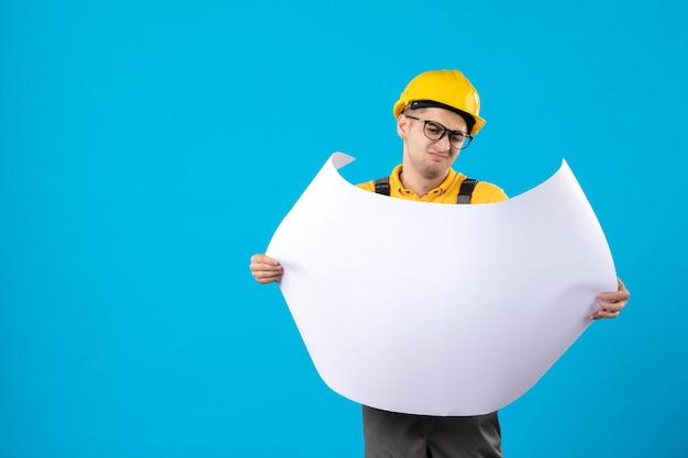Widok z przodu konstruktora w żółtym mundurze z planem na niebiesko