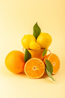 Widok z przodu kosz z cytrynami pokrojonymi w całości, świeży mellow i soczysty wraz z pomarańczowym plasterkiem na kremowym tle
