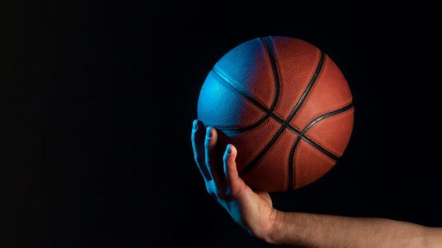 Widok z przodu koszykówki w posiadaniu męskiej ręki