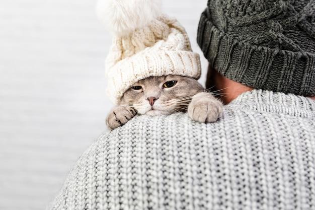 Widok z przodu kotek w męskich ramionach