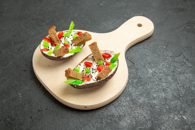 Widok z przodu kremowe awokado z pokrojoną papryką i kawałkami chleba na szarej przestrzeni