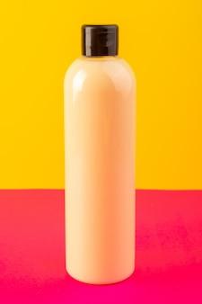 Widok z przodu kremowy szampon z plastikowej butelki z czarną nakrętką na różowo-żółtym tle kosmetyki do włosów