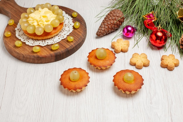 Widok z przodu kremowy tort z małymi słodkimi ciastkami i winogronami na białym biurku owocowe ciastko ciasto biszkoptowe