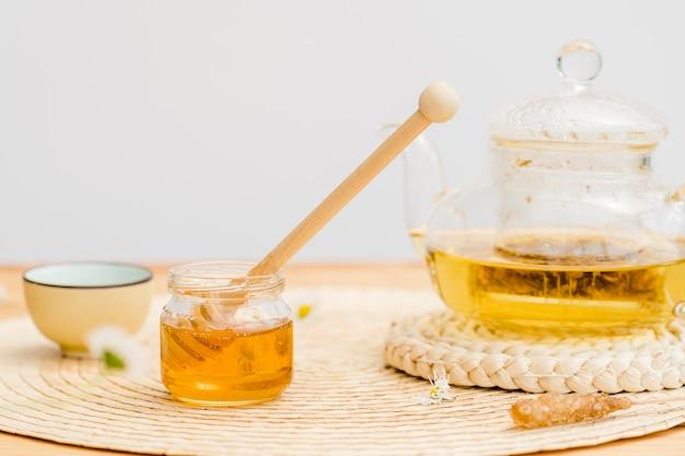 Widok z przodu kryształowy czajniczek i słoik miodu