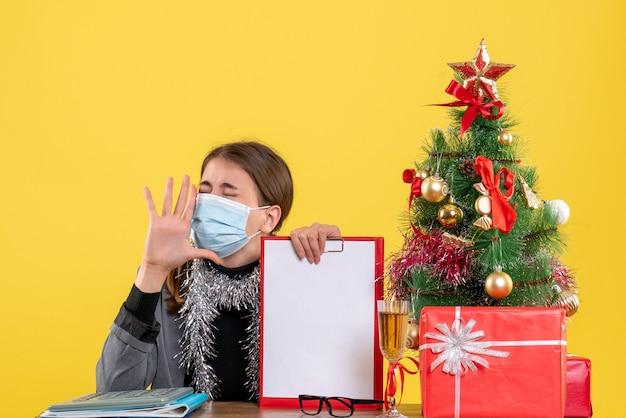Widok z przodu krzycząca dziewczyna z maską medyczną siedzi przy stole święta drzewo i prezenty koktajlowe