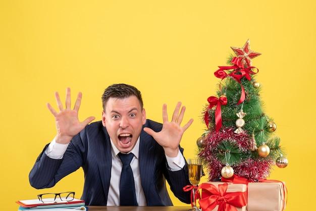 Widok z przodu krzyczącego młodego człowieka siedzącego przy stole w pobliżu choinki i prezentów na żółto