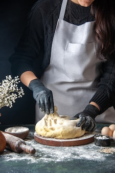 Widok z przodu kucharka rozwałkowująca ciasto na ciemnym cieście surowym cieście ciasto piekarnicze na gorąco