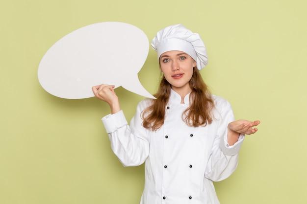 Widok z przodu kucharki na sobie biały garnitur kucharza, trzymając duży znak na zielonej ścianie
