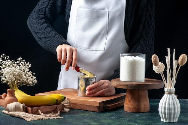 Widok z przodu kucharki próbującej otworzyć puszkę ze skondensowanym mlekiem na ciemnym tle