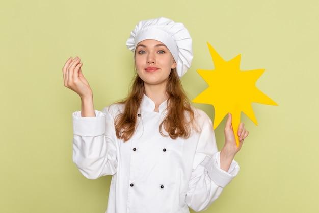 Widok z przodu kucharki w białym garniturze z żółtym znakiem na zielonej ścianie