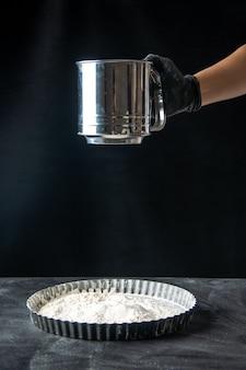 Widok z przodu kucharz siejący białą mąkę na patelnię na ciemnym jajku ciasto kuchnia piekarz robotnik praca