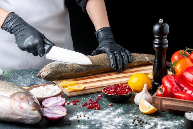 Widok z przodu kucharz sieka surową rybę na drewnianej desce młynek do pieprzu miska na mąkę nasiona granatu w misce na stole kuchennym