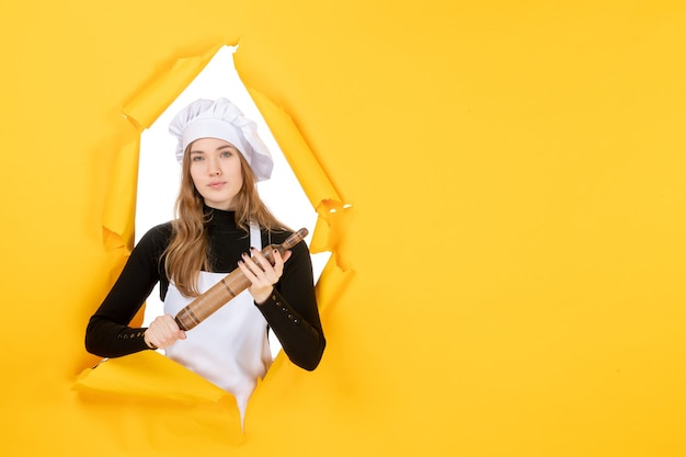 Widok z przodu kucharz trzyma wałek do ciasta na żółtym kolorze kuchni kuchnia jedzenie słońce zdjęcie