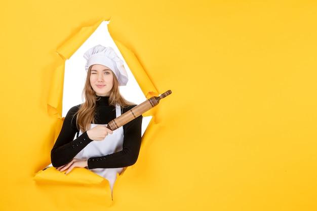Widok z przodu kucharz trzyma wałek do ciasta na żółtym kolorze kuchnia praca jedzenie słońce zdjęcie