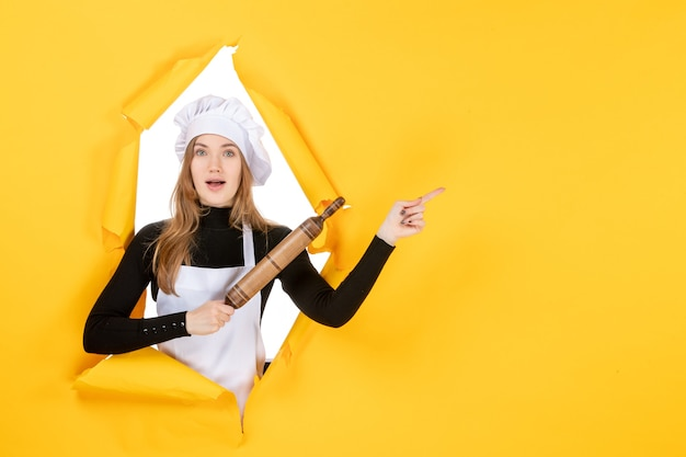 Widok z przodu kucharz trzyma wałek do ciasta na żółtym kolorze kuchnia praca kuchnia jedzenie słońce emocje