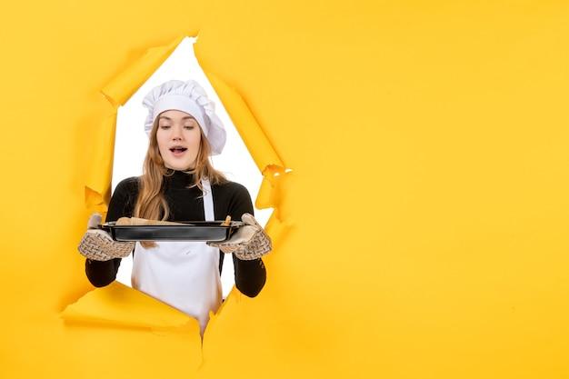 Widok z przodu kucharz trzymający czarną patelnię na żółtym słońcu jedzenie zdjęcie praca kuchnia emocje kuchnia kolor