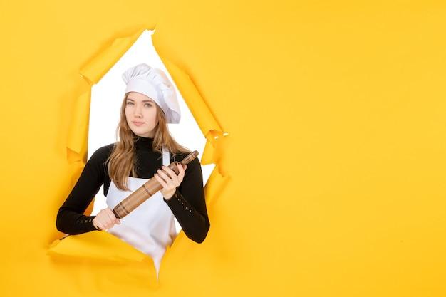 Widok z przodu kucharz trzymający wałek do ciasta na żółtym kolorze pracy kuchnia kuchnia jedzenie słońce zdjęcie