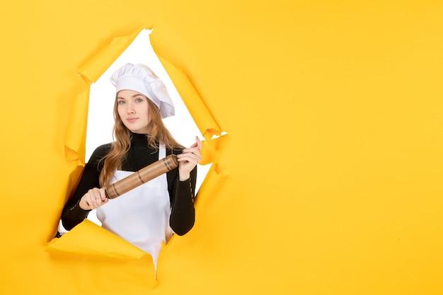 Widok z przodu kucharz trzymający wałek do ciasta na żółtym słońcu jedzenie kolor praca kuchnia zdjęcie emocja kuchnia