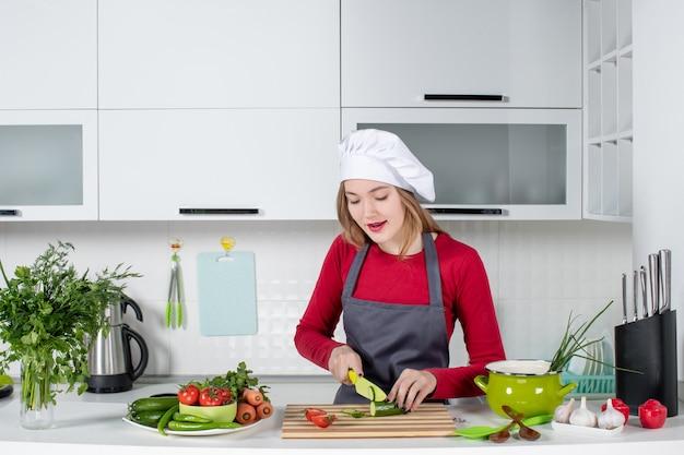 Widok z przodu kucharz w fartuchu krojący ogórek na desce?