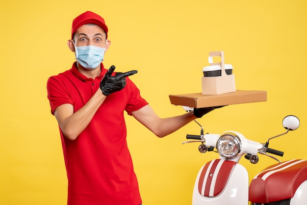 Widok z przodu kurier męski w masce z dostawą kawy i pudełkiem na żółtym kolorze mundur roboczy covid-wirus pandemiczny