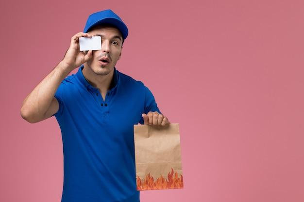 Widok z przodu kurier męski w niebieskim mundurze, trzymający paczkę z jedzeniem z plastikową kartą na różowej ścianie, dostawa munduru pracownika