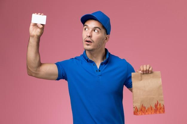 Widok z przodu kurier męski w niebieskim mundurze trzymający pakiet żywności z kartą na różowej ścianie, dostawa usług mundurowych