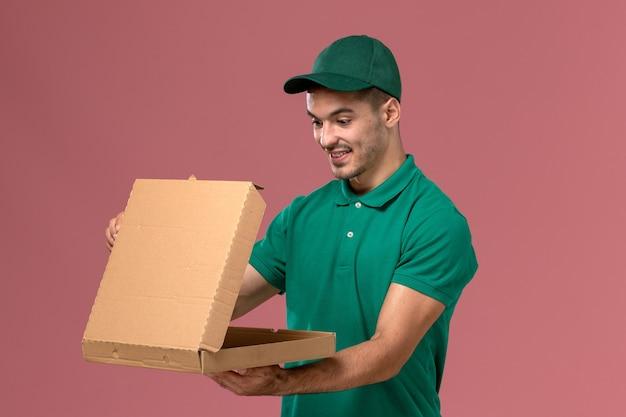 Widok z przodu kurier męski w zielonym mundurze, trzymając pudełko dostawy żywności na różowym tle