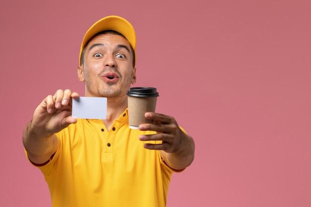 Widok z przodu kurier męski w żółtym mundurze, trzymając filiżankę kawy dostawy i białą kartkę na różowym tle