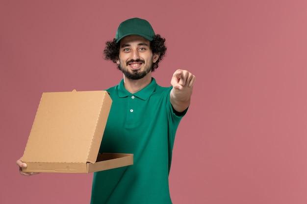 Widok z przodu kurier mężczyzna w zielonym mundurze i pelerynie trzymający dostawę pudełko z jedzeniem na różowym biurku pracownik jednolity dostawy