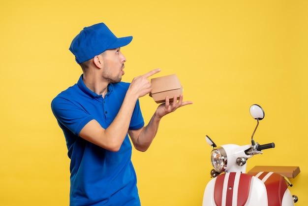 Widok z przodu kurier płci męskiej trzymający mały pakiet żywności na żółtych kolorach pracy mundur służbowy pracownik rowerowy