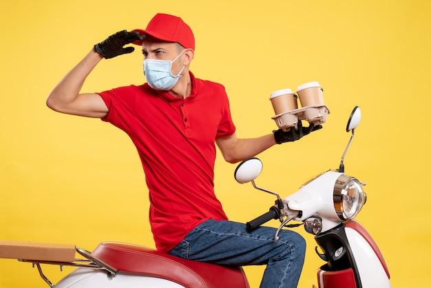 Widok z przodu kurier w mundurze i masce z kawą na żółtych barwach zleca pandemię wirusa w usługach gastronomicznych