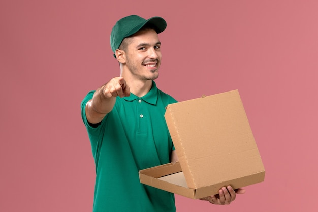 Widok z przodu kurier w zielonym mundurze, trzymając i otwierając pudełko z jedzeniem na jasnoróżowym tle