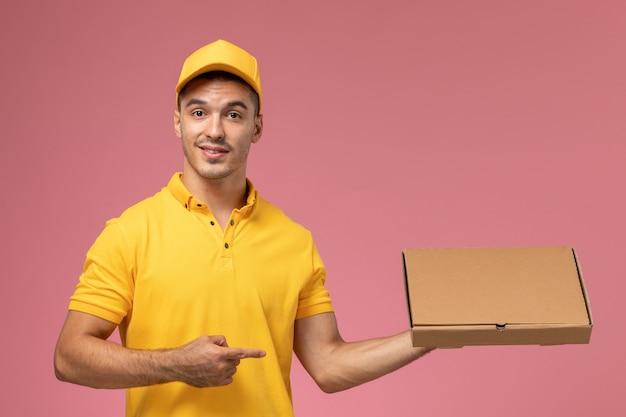 Widok z przodu kurier w żółtym mundurze, trzymając pudełko dostawy żywności na różowym tle