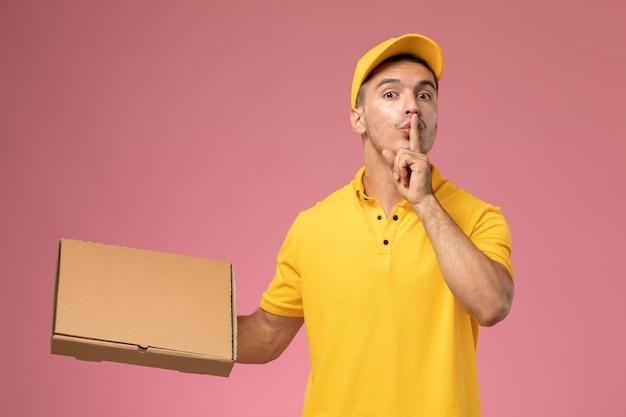 Widok z przodu kurier w żółtym mundurze, trzymając pudełko z dostawą jedzenia i prosząc o ciszę na różowym tle