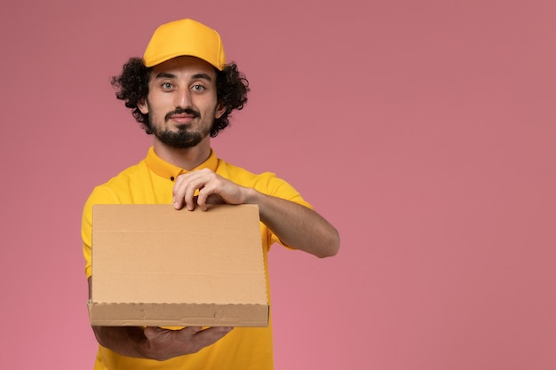 Widok z przodu kurier w żółtym mundurze, trzymający pudełko z dostawą jedzenia na jasnoróżowej ścianie