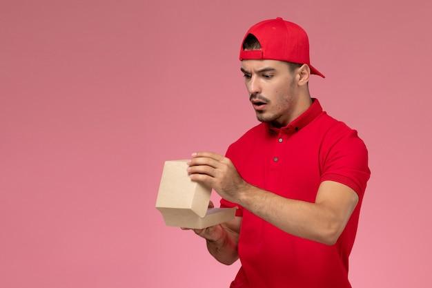 Widok z przodu kuriera w czerwonym mundurze i czapce trzymającej małą przesyłkę