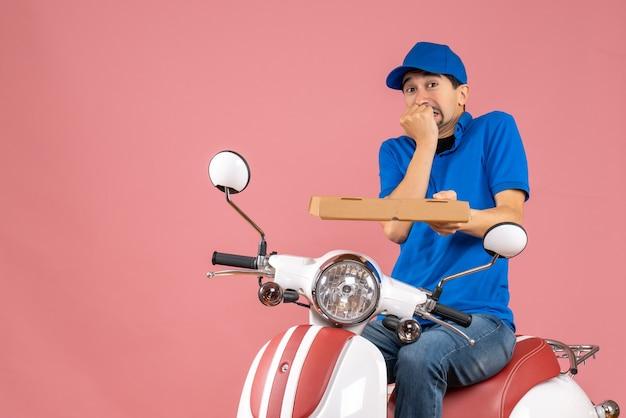 Widok z przodu kuriera w kapeluszu siedzi na skuterze, czując się przestraszony na pastelowym brzoskwiniowym tle