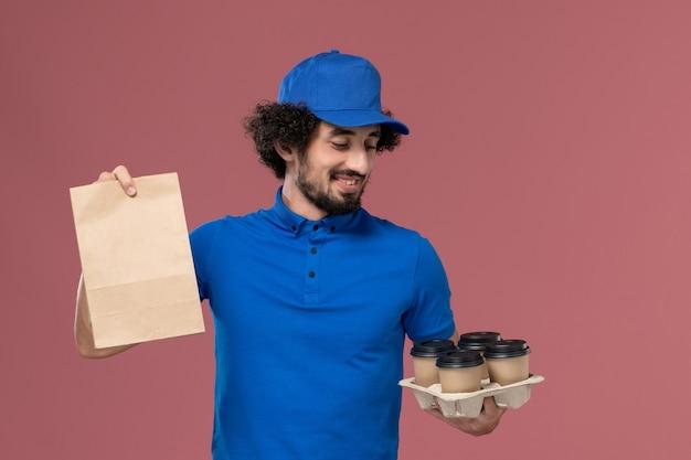 Widok z przodu kuriera w niebieskiej czapce mundurowej z filiżankami kawy dostawy i opakowaniem żywności na rękach na różowej ścianie