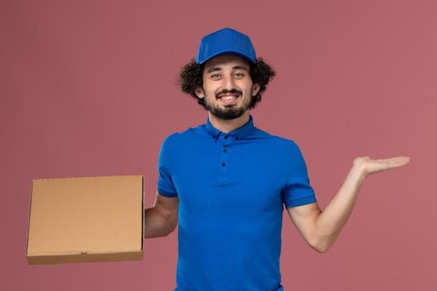 Widok z przodu kuriera w niebieskiej czapce mundurowej z pudełkiem na żywność na rękach na jasnoróżowej ścianie