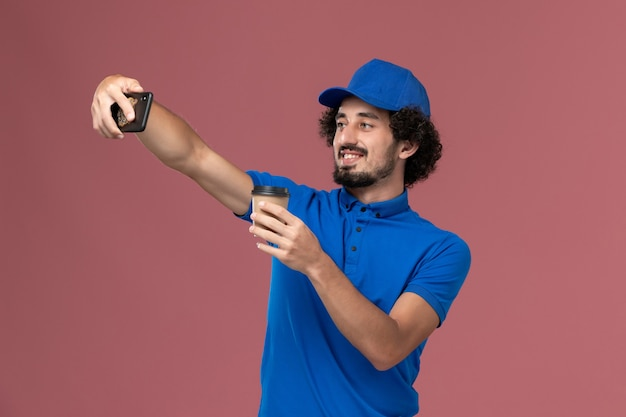 Widok z przodu kuriera w niebieskim mundurze i czapce z filiżanką kawy na rękach i robieniem zdjęcia na różowej ścianie
