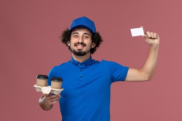 Widok z przodu kuriera w niebieskim mundurze i czapce z filiżankami do kawy i kartą na rękach na różowej ścianie