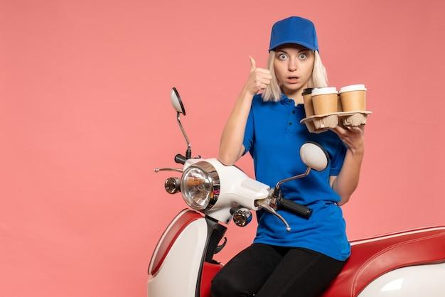 Widok z przodu kurierka na rowerze z filiżankami kawy na różowo