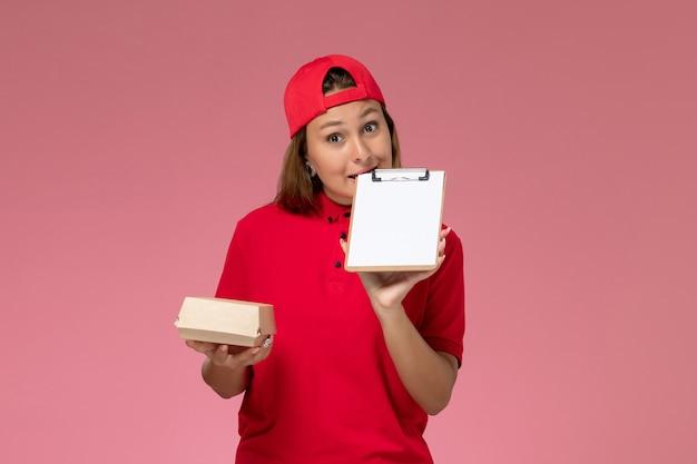 Widok z przodu kurierka w czerwonym mundurze i pelerynie trzymająca małą paczkę z dostawą żywności i notatnik na różowej ścianie, jednolita firma kurierska