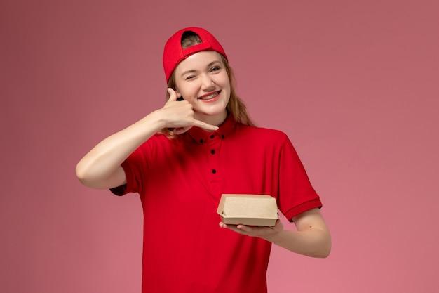 Widok z przodu kurierka w czerwonym mundurze i pelerynie trzymająca małą paczkę z dostawą żywności na różowej ścianie, firma kurierska jednolita praca